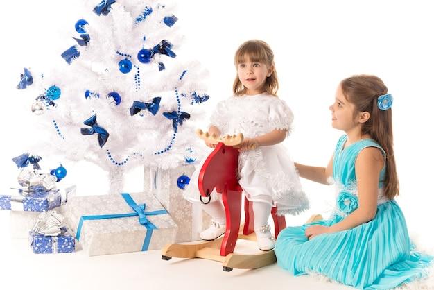 Glückliche positive kleine mädchenschwestern, die geschenkboxen halten, während sie nahe einem weißen künstlichen weihnachtsbaum auf einer weißen oberfläche sitzen