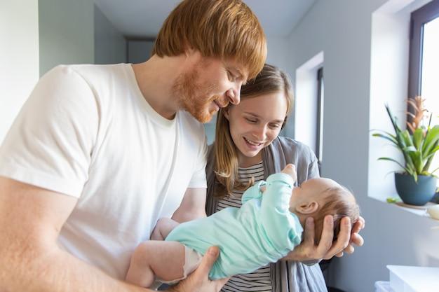 Glückliche positive neue eltern, die baby in den armen streicheln