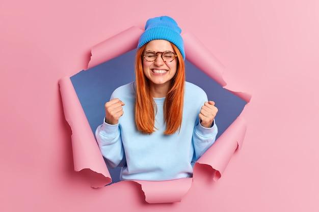 Glückliche positive rothaarige frau ballt fäuste vor freude schließt die augen und fühlt sich sehr aufgeregt feiert erfolg trägt blaue pullover hut brille modelle durch papier