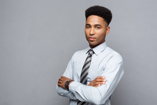Glückliche professionelle afroamerikaner geschäftsmann zuversichtlich arme verschränkt.