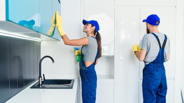 Glückliche professionelle junge mann und hübsche frau reiniger in der blauen arbeitskleidung, die die möbel mit lappen und spray in der zeitgenössischen küche säubert.