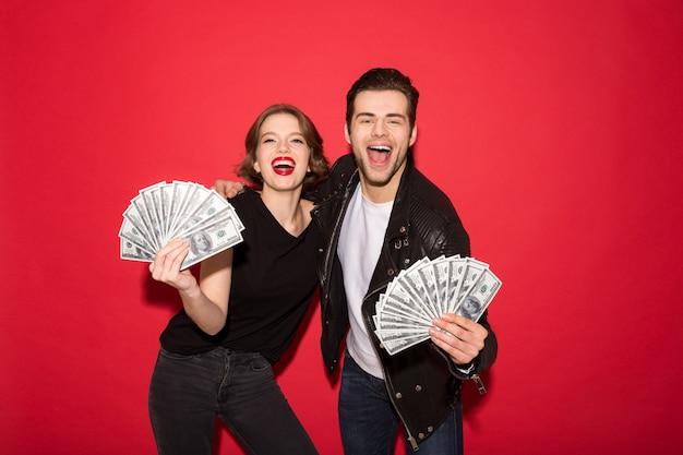 Glückliche punkpaare, die geld und das schauen zeigen