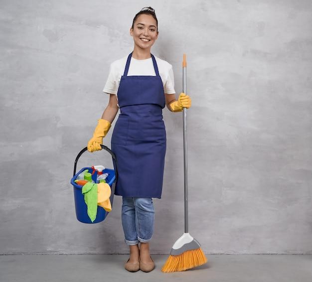 Glückliche putzfrau in uniform und gelben gummihandschuhen mit besen und plastikeimer mit