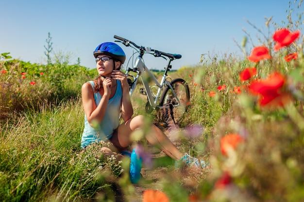 Glückliche radfahrerin, die ihren helm abnimmt, nachdem sie fahrrad im sommermohnfeld reitet.