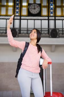 Glückliche recht junge frau, die selfie foto in der stationshalle macht