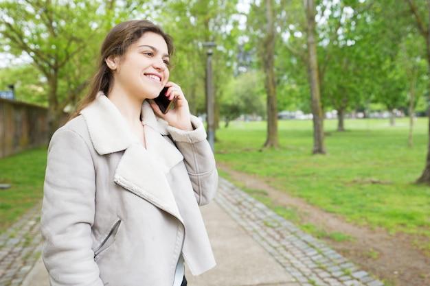 Glückliche recht junge frau, die um smartphone im park ersucht