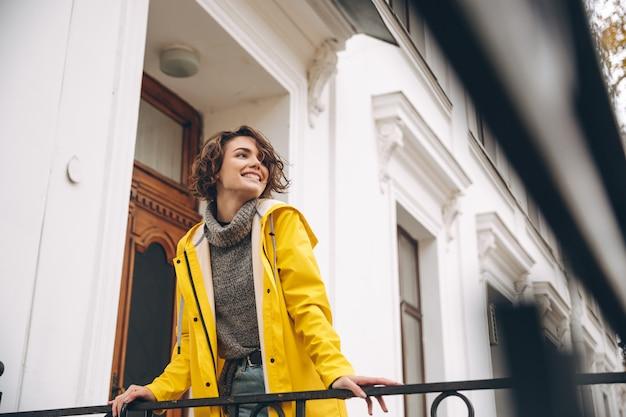 Glückliche recht junge frau kleidete im gelben regenmantel an