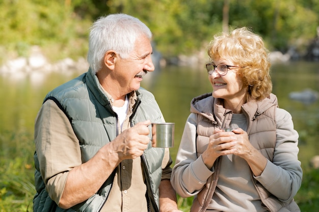 Glückliche reife aktive wanderer mit heißem tee, die einander betrachten, während ruhe an sonnigem tag genießen