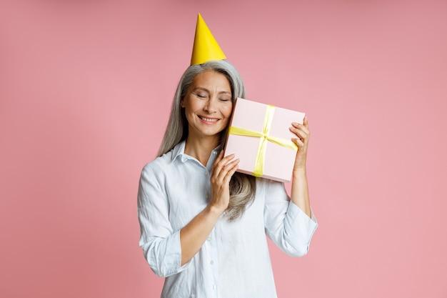 Glückliche reife asiatische dame mit gelbem partyhut hält geschenkbox auf rosa hintergrund
