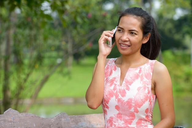 Glückliche reife asiatische frau, die am telefon im park draußen spricht