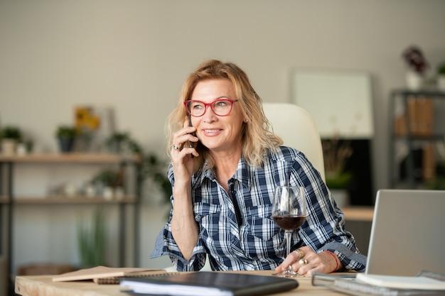 Glückliche reife blonde frau mit smartphone und glas rotwein sitzen am schreibtisch vor laptop, während am telefon zu hause gesprochen