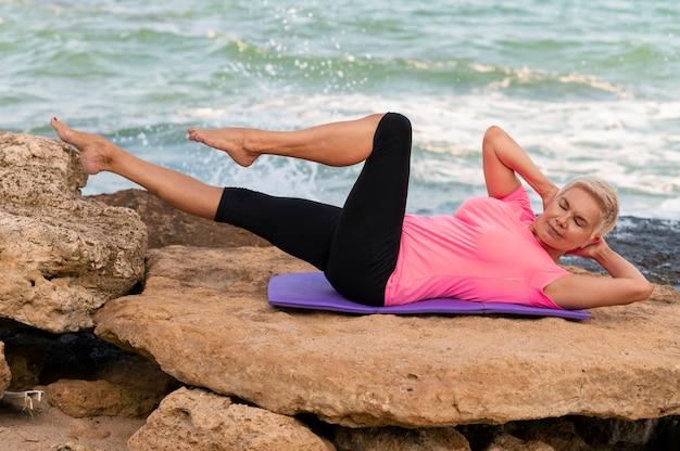 Glückliche reife frau am meer machen pilates-übungen auf yogamatte