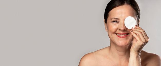 Glückliche reife frau, die mit wattepad für make-up-entfernung und kopierraum aufwirft