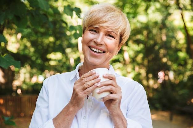 Glückliche reife frau, die tasse kaffee hält