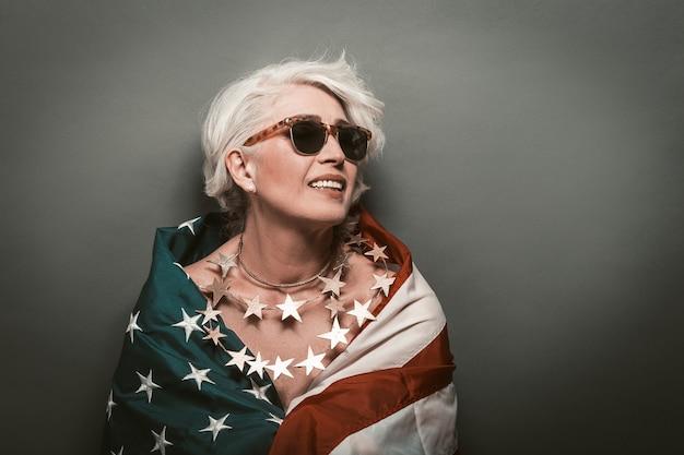 Glückliche reife frau, die usa-flagge trägt. schöne ältere dame in perle von sternen und sonnenbrille zahniges lächeln