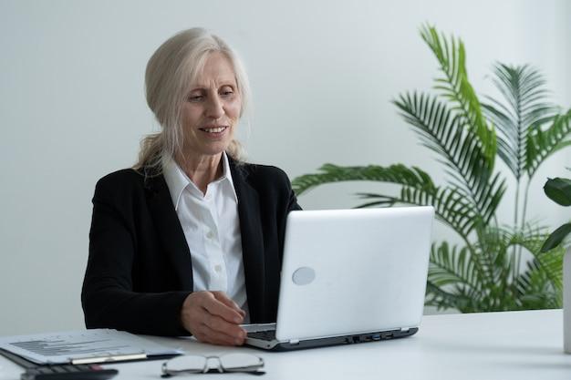 Glückliche reife frau feiert online-sieg mit einem laptop, während sie an ihrem arbeitsplatz im büro sitzt