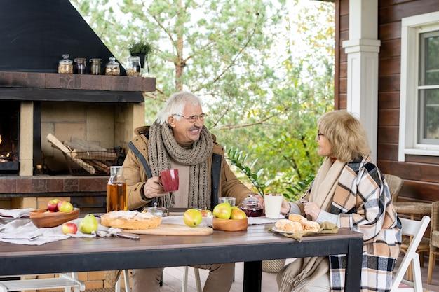 Glückliche reife frau in brillen und warmer freizeitkleidung, die ihren mann anschaut, während sie beide tee mit hausgemachten snacks gegen den kamin trinken?