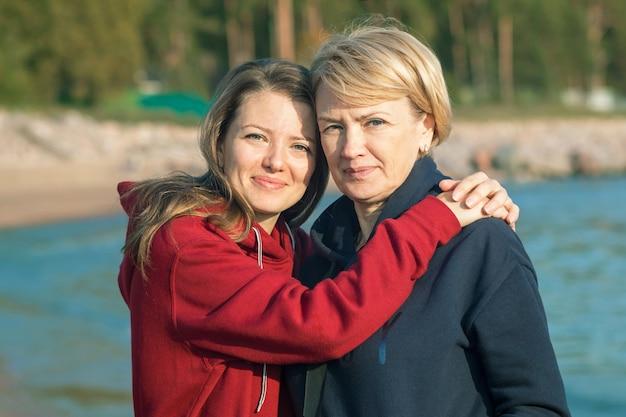 Glückliche reife frau mit ihrer erwachsenen tochter, die am strand am meer umarmt.