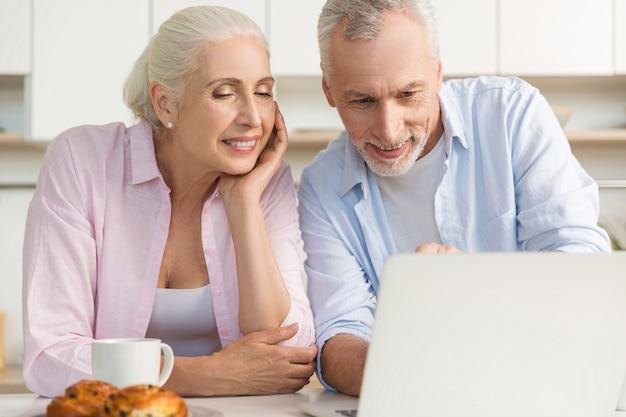 Glückliche reife liebende paarfamilie, die laptop-computer verwendet