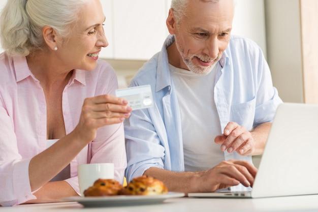 Glückliche reife liebende paarfamilie, die laptop hält kreditkarte