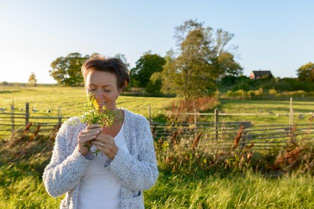 Glückliche reife schöne frau, die blumen in der friedlichen grasebene mit natur riecht