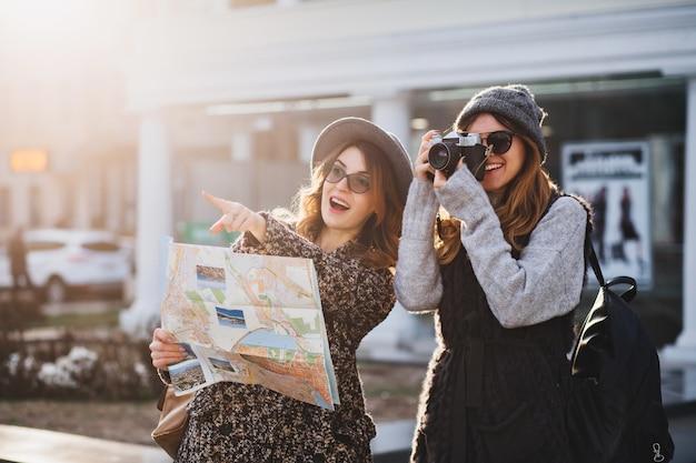 Glückliche reise zusammen von zwei modischen frauen im sonnigen stadtzentrum. junge freudige frauen, die positivität ausdrücken, karte verwenden, urlaub mit taschen, kamera, foto machen, fröhliche gefühle, gute stimmung.