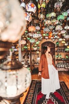 Glückliche reisefrau, die erstaunliche traditionelle handgemachte türkische lampen wählt