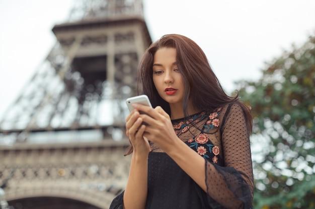 Glückliche reisefrau, die smartphone nahe dem eiffelturm und karussell, paris verwendet. porträt der reise