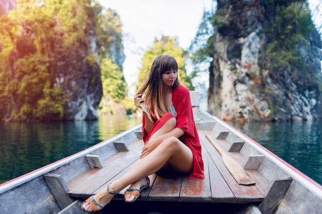 Glückliche reisefrau, die wilde natur des khao sok nationalparks erforscht. sitzen in holz long tail boot auf tropischen kalksteinfelsen. insellagune.