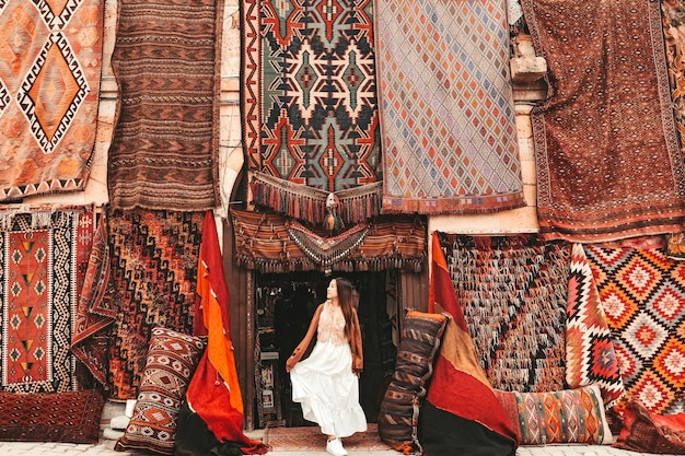 Glückliche reisefrau mit erstaunlichen bunten teppichen im lokalen teppichshop, goreme. kappadokien türkei