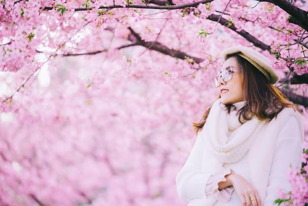 Glückliche reisefrau und -lächeln mit kirschblüte-kirschblütenbaum im urlaub während frühling, asiatisch