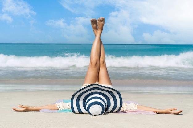 Glückliche reisende asiatin genießt im urlaub am tropischen strand ein sonnenbad. sommer am strandkonzept.