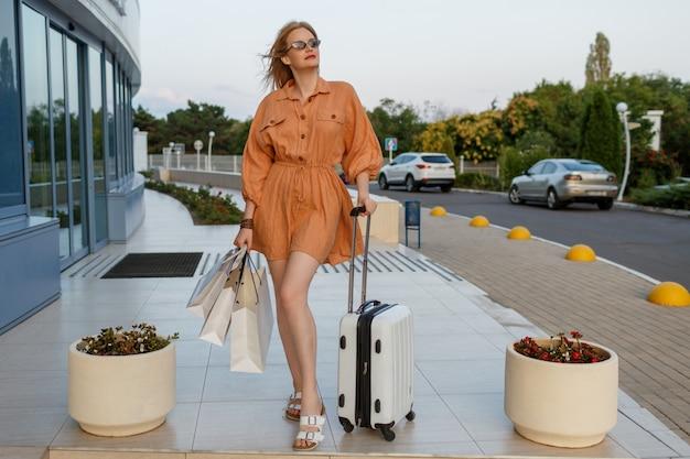 Glückliche reisende dame mit weißen einkaufstaschen, die über flughafen stehen