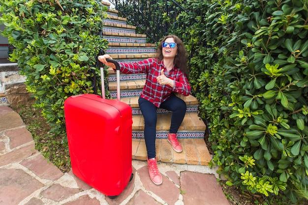 Glückliche reisende frau, die auf treppen in den sonnigen gläsern sitzt