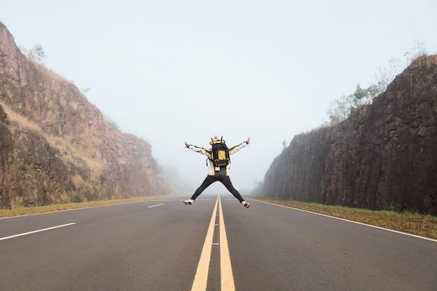 Glückliche reisende frau, die mit ausgestreckten beinen und armen springt.