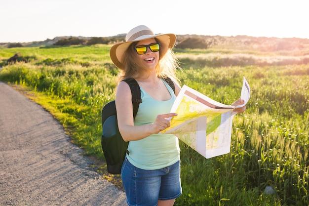 Glückliche reisende mit rucksack überprüft die karte, um eine wegbeschreibung zu finden