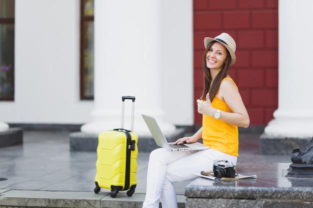 Glückliche reisende touristische frau in freizeitkleidung, hut mit koffer sitzen mit laptop-pc-computer, der daumen in der stadt im freien zeigt. mädchen, das am wochenende ins ausland reist. tourismus reise lebensstil.