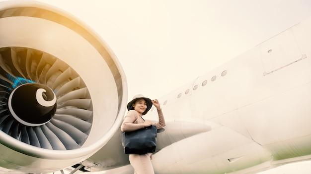 Glückliche reisepassagier-asien-frau, die vor dem flugzeug steht.