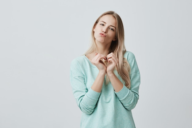 Glückliche reizende frau mit blondem langem haar, das liebeszeichen mit ihren in herzform hohlen händen zeigt. kaukasische frau in der liebe schmollende lippen, küsse senden, positive emotionen ausstrahlen.