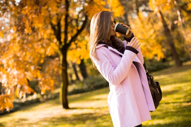 Glückliche reizende junge frau, die kaffee im freien im herbstpark trinkt