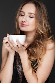 Glückliche reizende junge frau, die tasse kaffee steht und hält