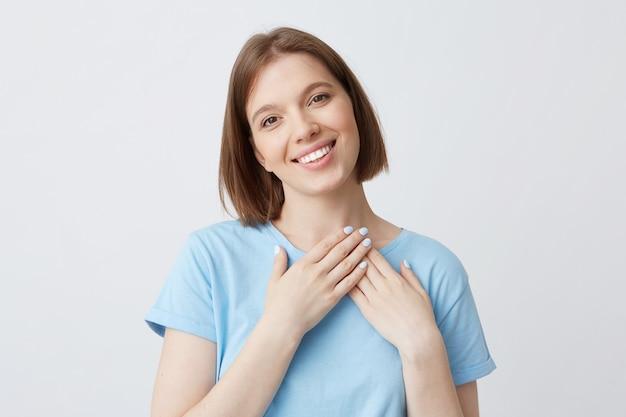 Glückliche reizende junge frau im blauen t-shirt legte hände auf ihren herzbereich und lächelte