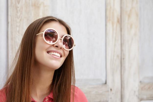 Glückliche romantische junge frau in der stilvollen runden sonnenbrille mit spiegelgläsern, die mit inspiriertem freudigem lächeln nach oben schauen.