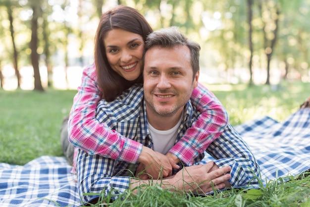 Glückliche romantische paare, die auf blauer decke am park betrachtet kamera liegen