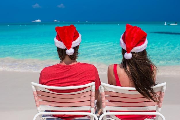 Glückliche romantische paare in roter santa hats am tropischen strand