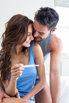 Glückliche romantische paare mit schwangerschaftstest