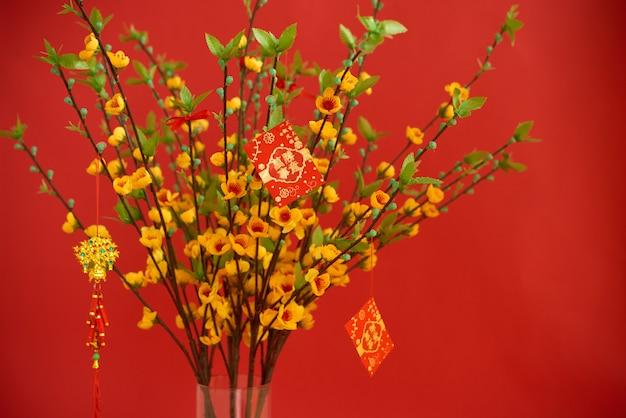 Glückliche rote umschläge, die an blühendem pfirsichbaum mit besten wünschen für bevorstehendes jahr auf karten hängen