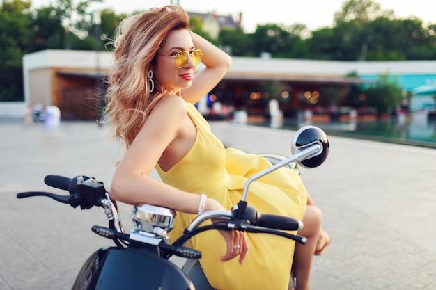 Glückliche rothaarige frau im gelben kleid, das auf ihrem elektroroller entspannt, während urlaubszeit in der modernen stadt verbringt. romantische stimmung.