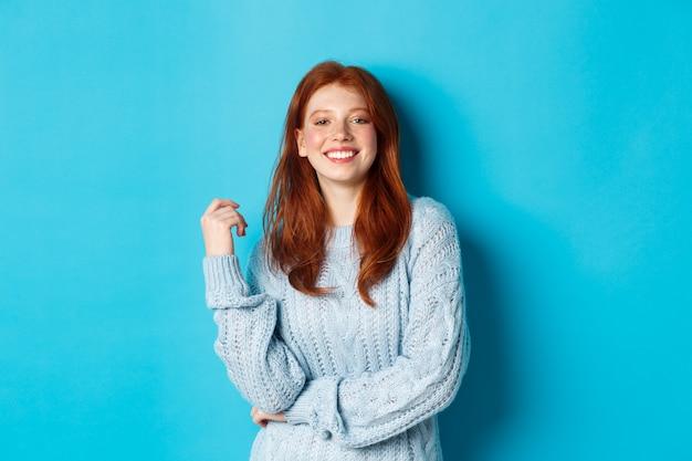 Glückliche rothaarige frau im pullover, die kamera erfreut und lächelnd steht und gegen blauen hintergrund steht.