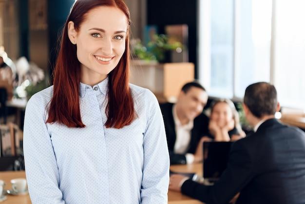 Glückliche rothaarige frau ist im vordergrund im büro